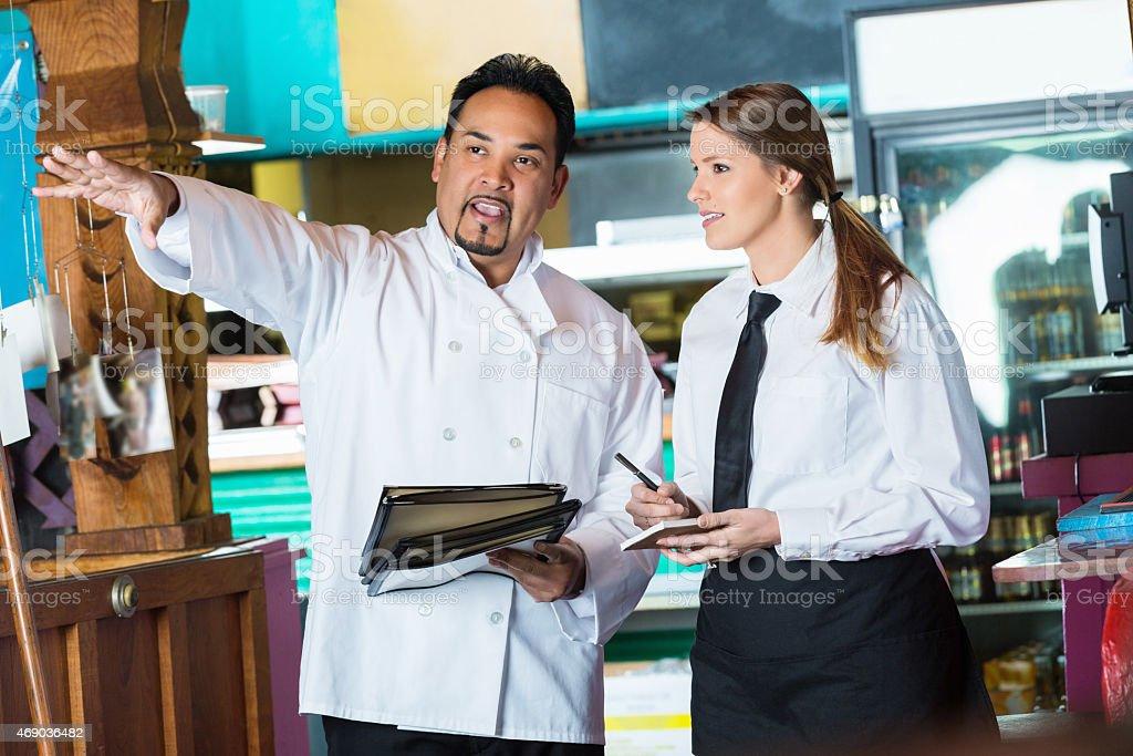 Restaurant chef training new waitress while explaining Mexican cuisine menu stock photo