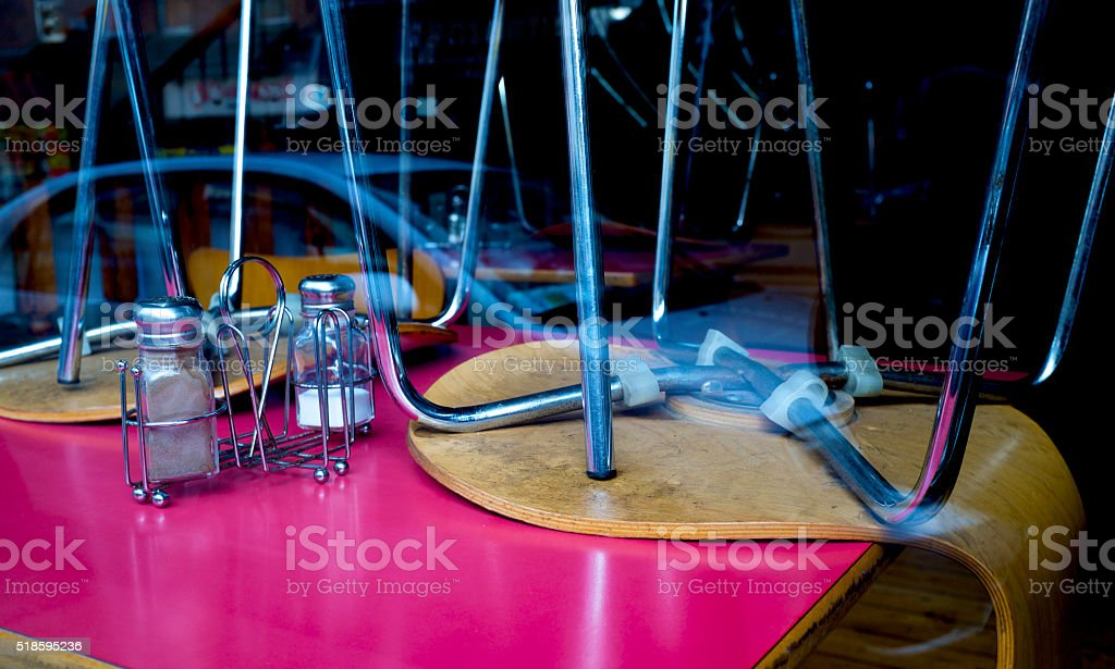 restaurant closed with the chairs on the table trough window stock photo