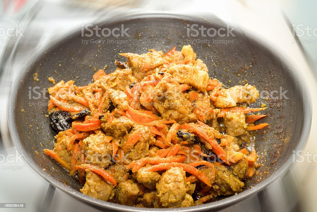 Restaurant cooking meat with carrot in frying pan stock photo