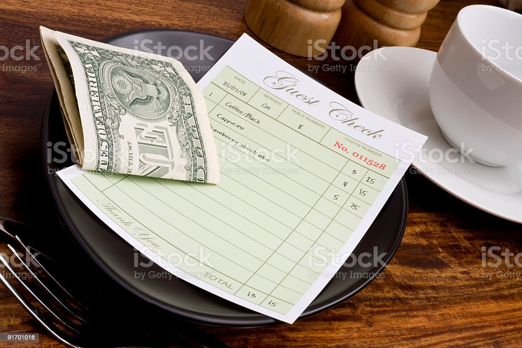 Restaurant guest check with folded dollar bills stock photo