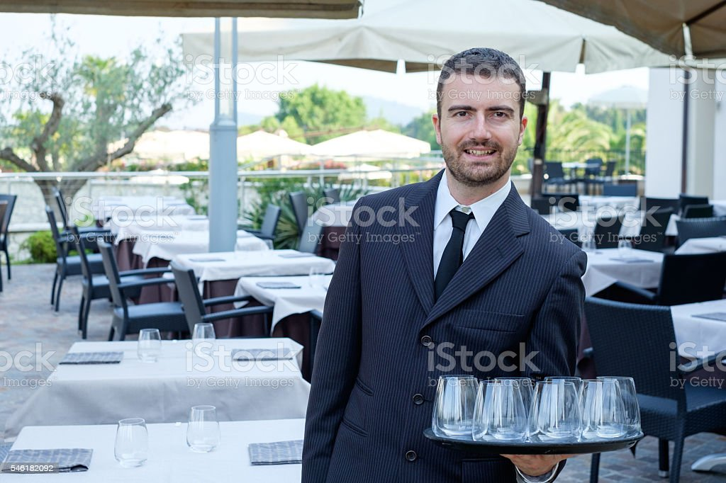 Restaurant male waiter with a tray of glasses stock photo