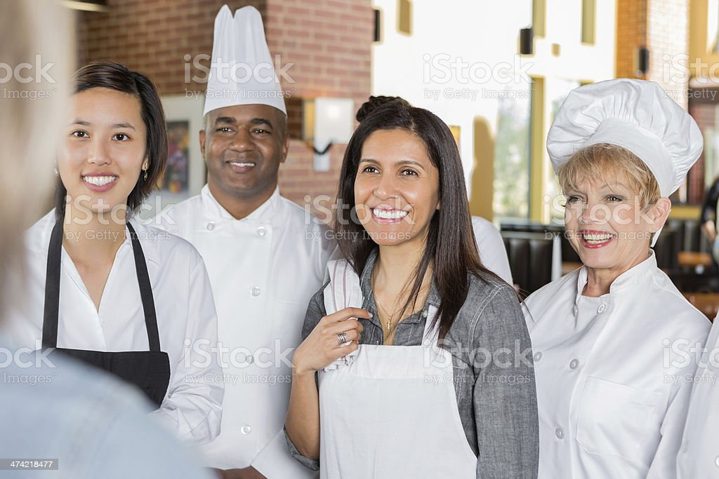 Restaurant manager giving instructions to chefs and waitstaff stock photo