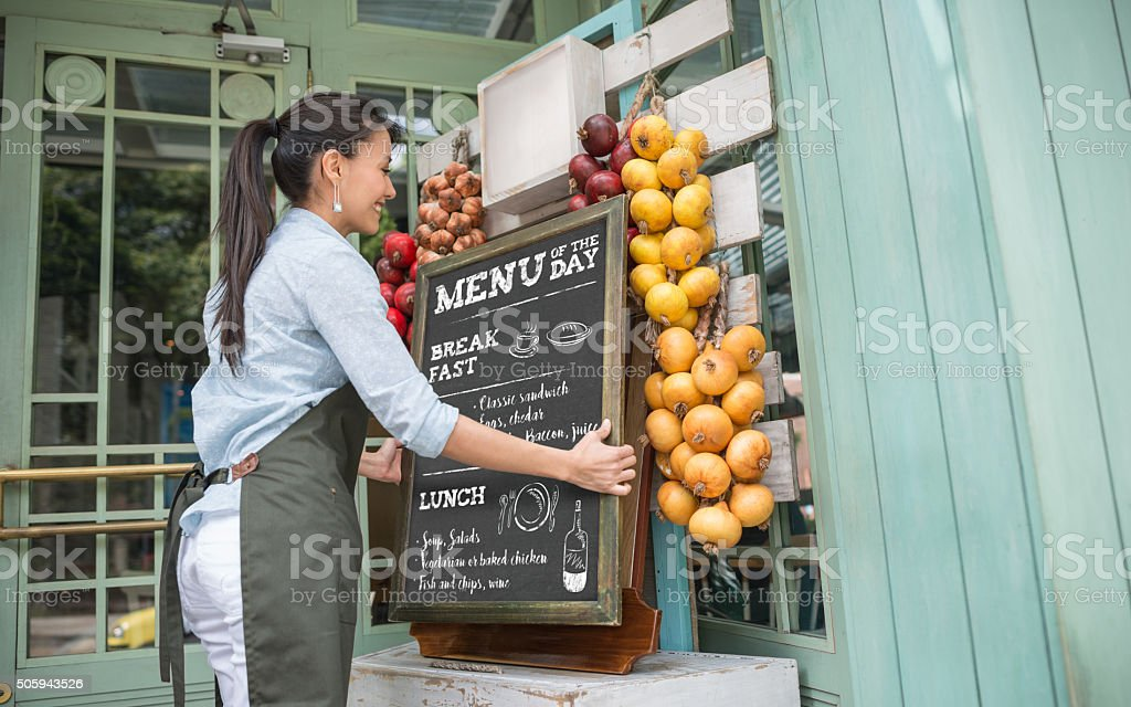 Restaurant manager hanging the menu at the entrance stock photo