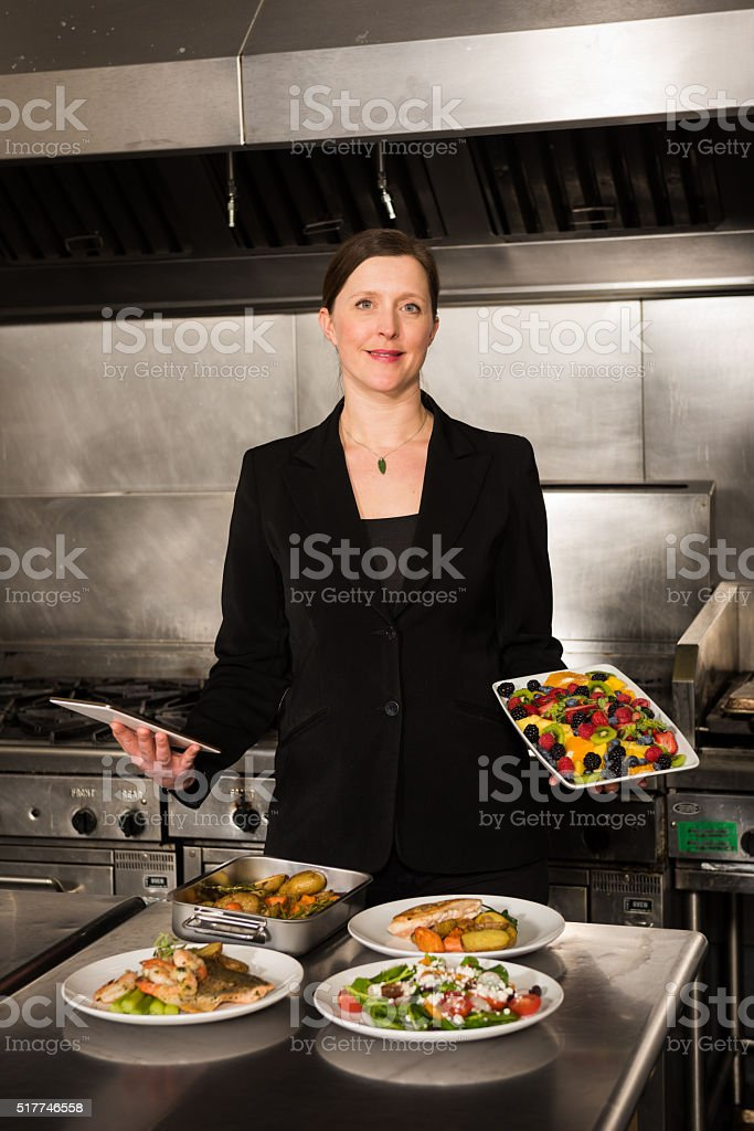 Restaurant Manager with prepared dishes and a tablet stock photo