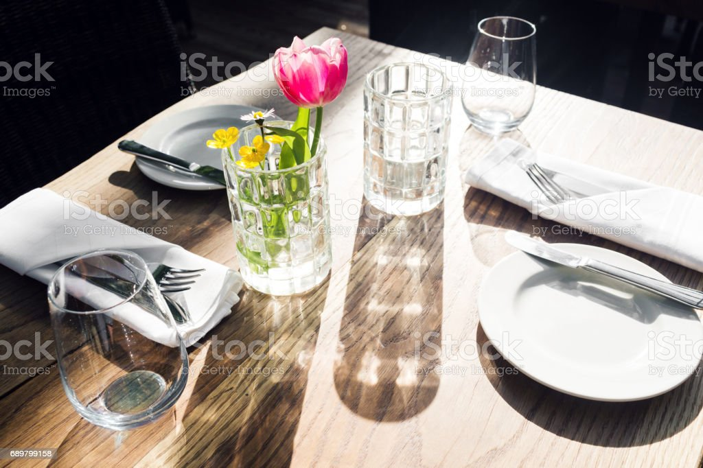 restaurant on the canal Venice. Tulip in a vase. table setting for a lovey dinner. Empty glasses set in cafe. Part of interior. napkins, plates, and cutlery. stock photo