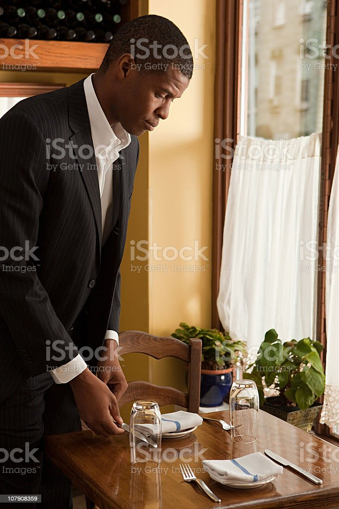 Restaurant owner setting the table stock photo