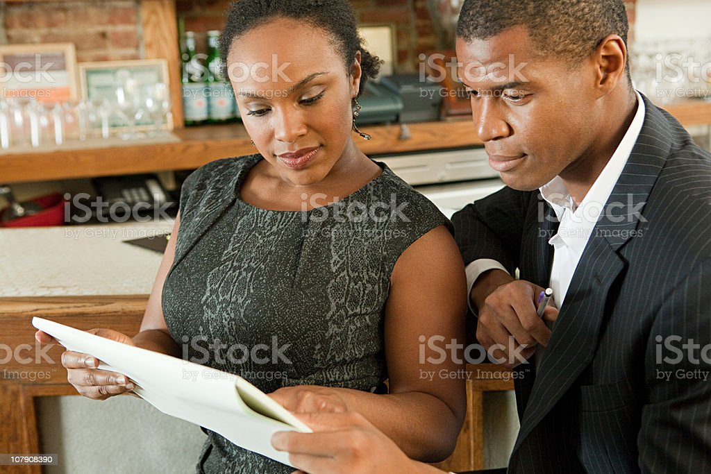 Restaurant owners looking at paperwork stock photo
