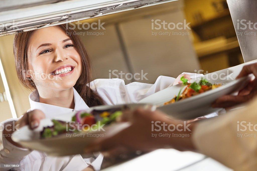 Restaurant server taking customer's food from chef stock photo