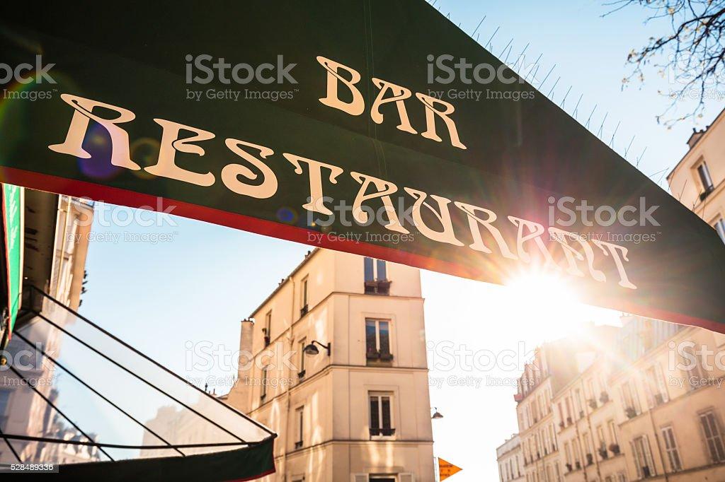 Restaurant sign against sun in Paris, France stock photo