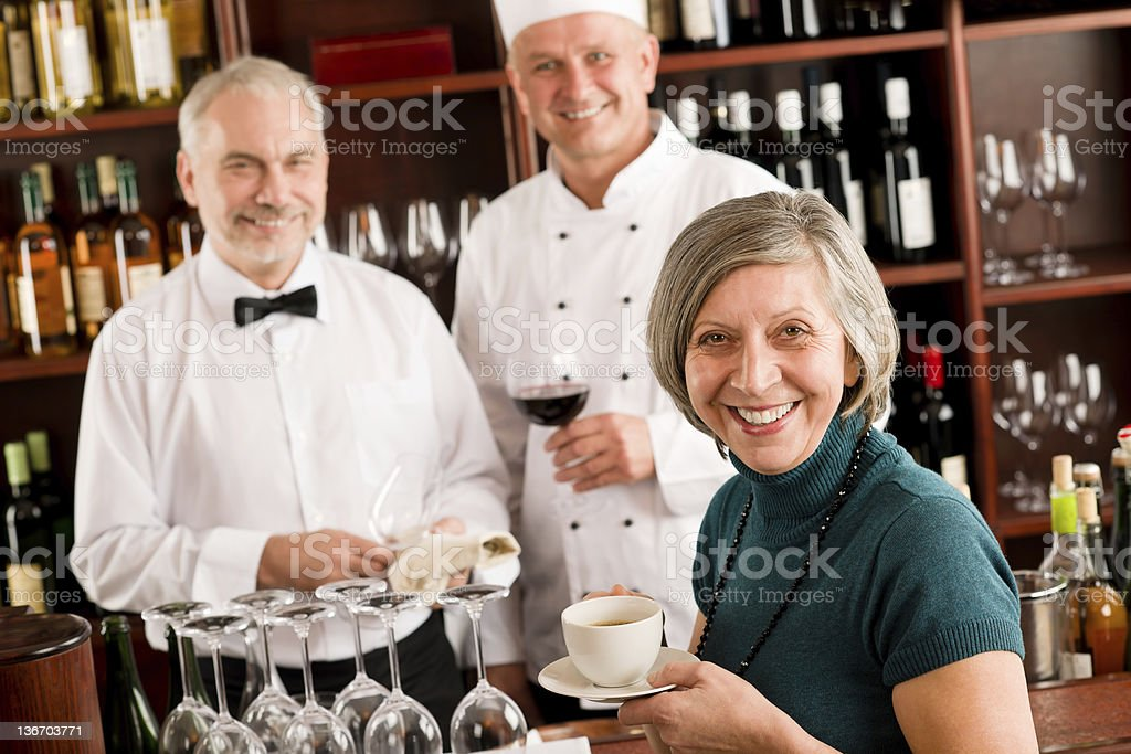 Restaurant smiling manager with staff wine bar royalty-free stock photo