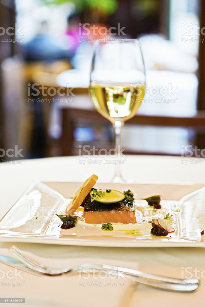 Restaurant table laid with elegant salmon dish and white wine stock photo