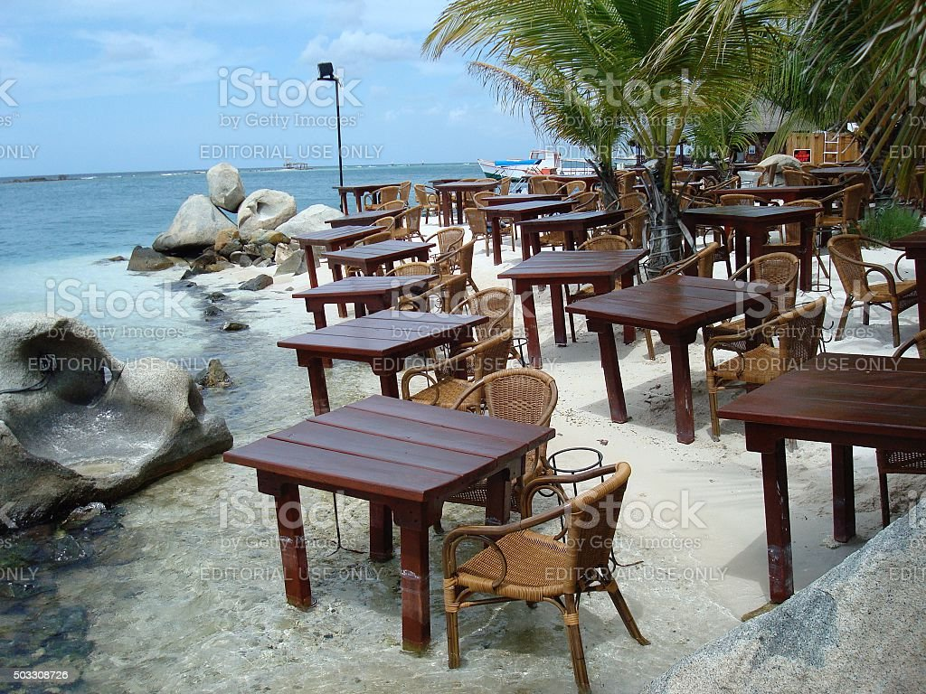 Restaurant tables and chairs in the sand stock photo