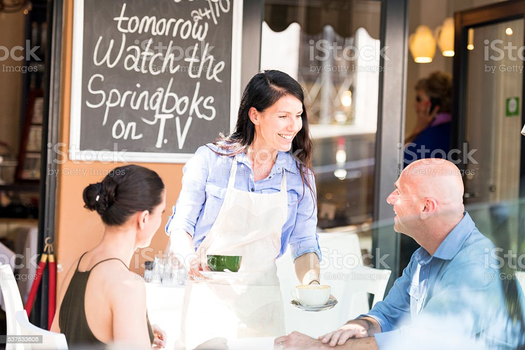 Restaurant Waitress Serving Coffee To Her Customers stock photo