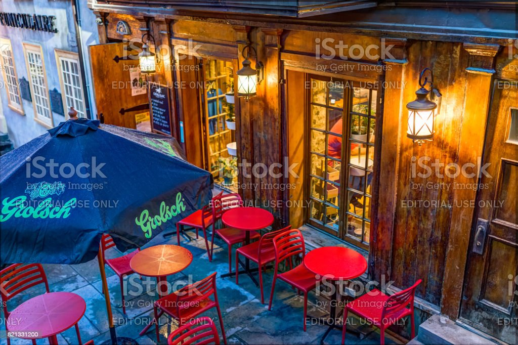 Restaurant with Grolsch sign and red chairs outside during blue hour by lower old town street called Rue du Petit Champlain on Escalier Casse-Cou stock photo