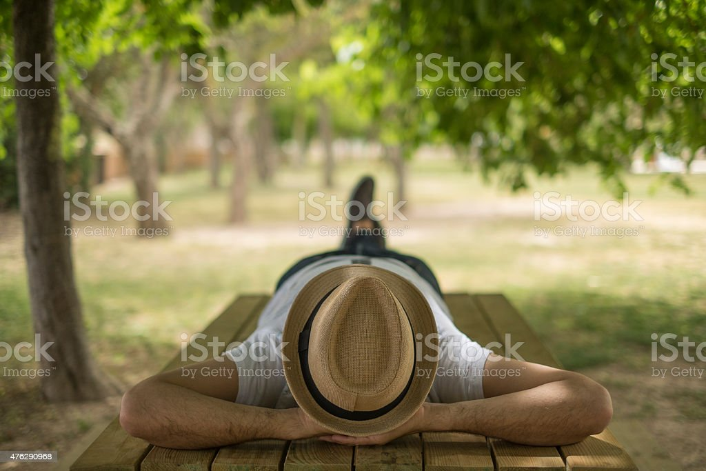 Restful boy laying down on a park wearing a hat stock photo