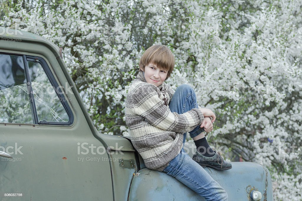 Resting teenager wearing woolly hand-knitted deer sweater in fruit garden stock photo