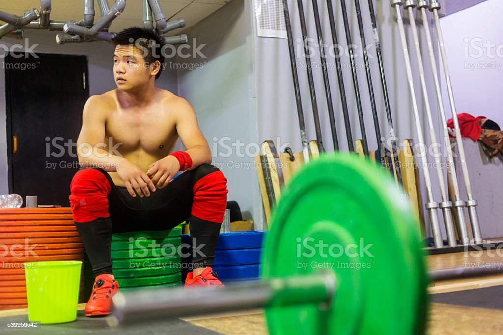 Resting Weightlifter Sits on Weight Plates Before Continuing his Training stock photo