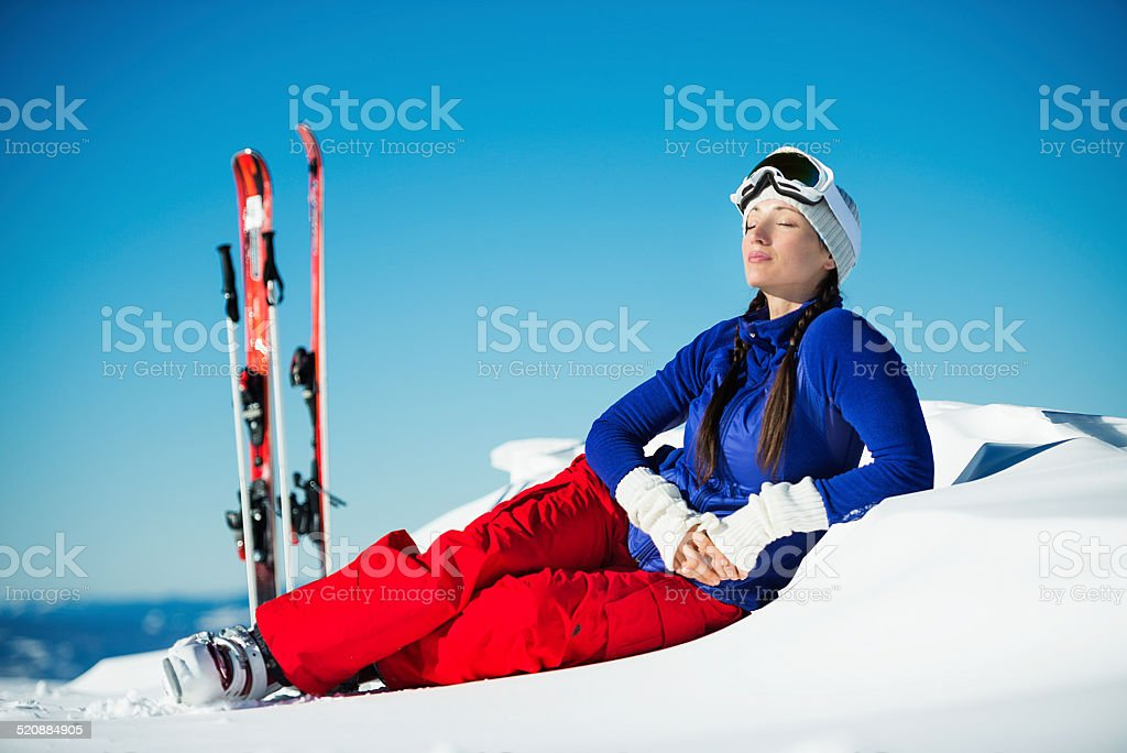 Resting woman lying in the snow stock photo