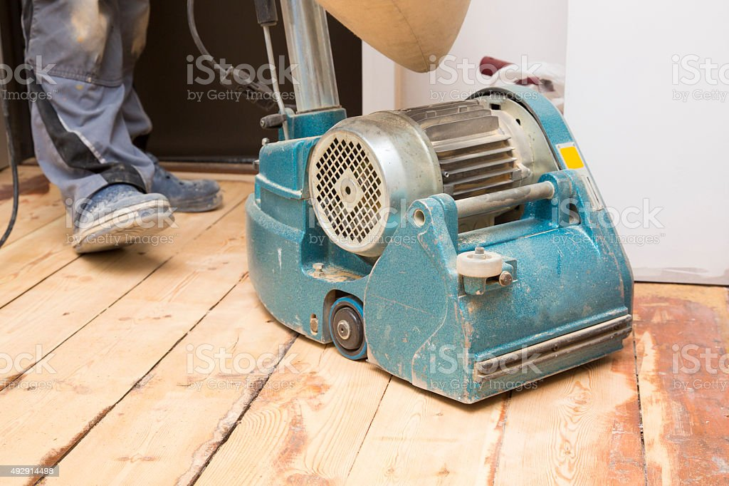 restore the old plank floor with grinding machine stock photo