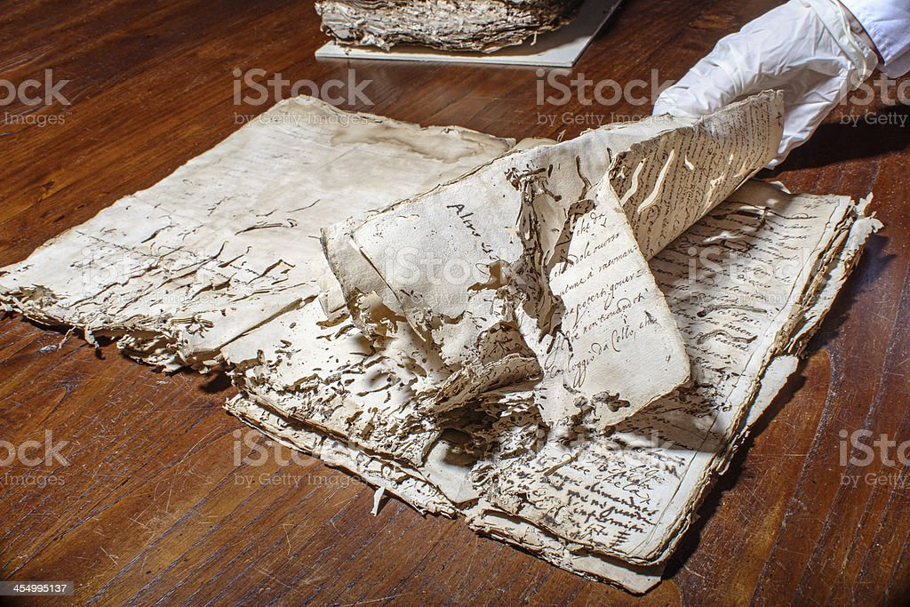 Restorer's hand browses ancient manuscript royalty-free stock photo