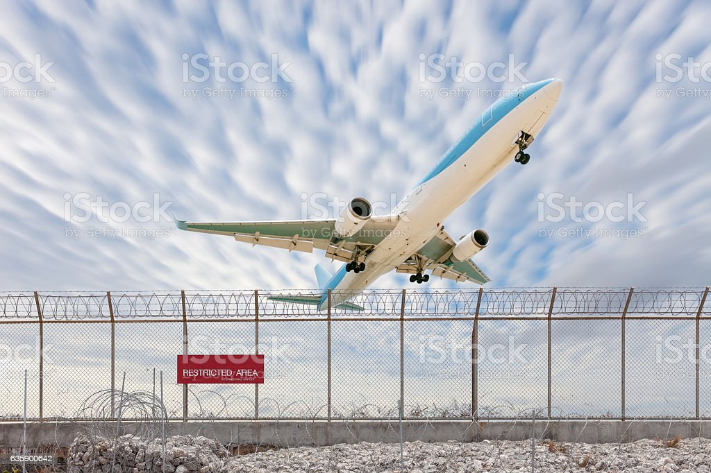 Restricted area fence and Passenger airplane landing stock photo
