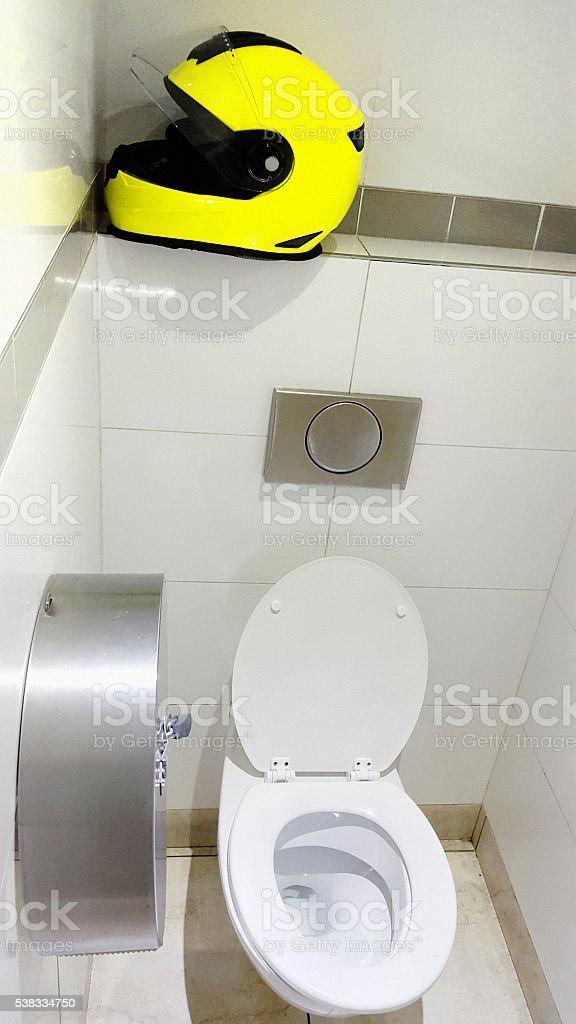 Restroom bathroom public toilet, motorbike crash helmet, stock photo
