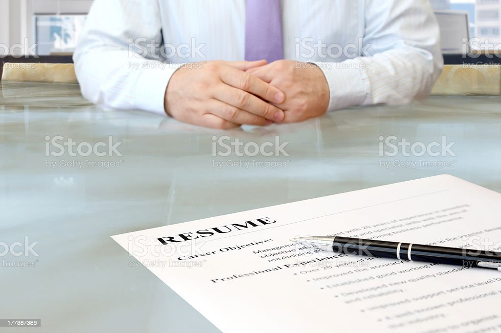 Resume and pen sitting on desk opposite of employer royalty-free stock photo