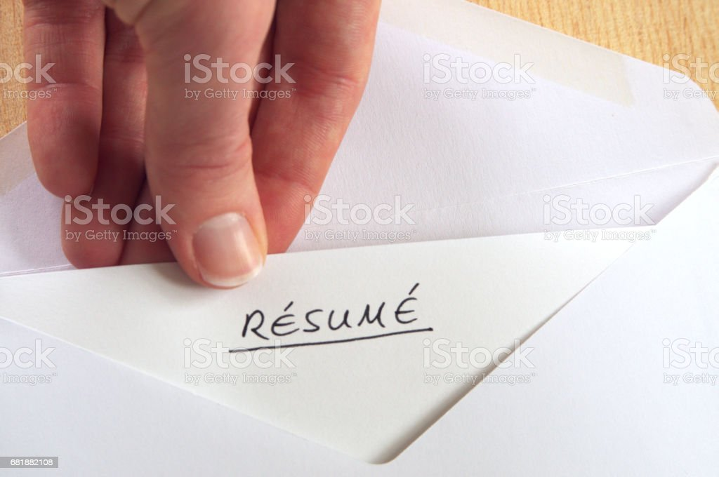 Resume in handwriting in white envelope, hand receiving letter, wooden background stock photo