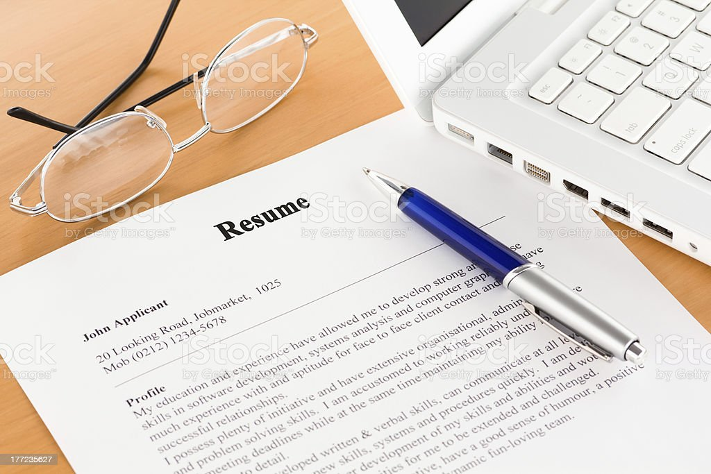 Resume with Pen by Laptop stock photo