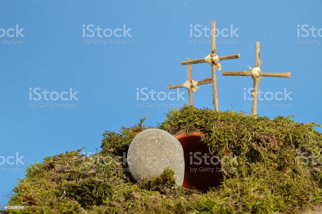 resurrection garden as easter decoration with a stone near the empty tomb and three crosses on a hill above stock photo