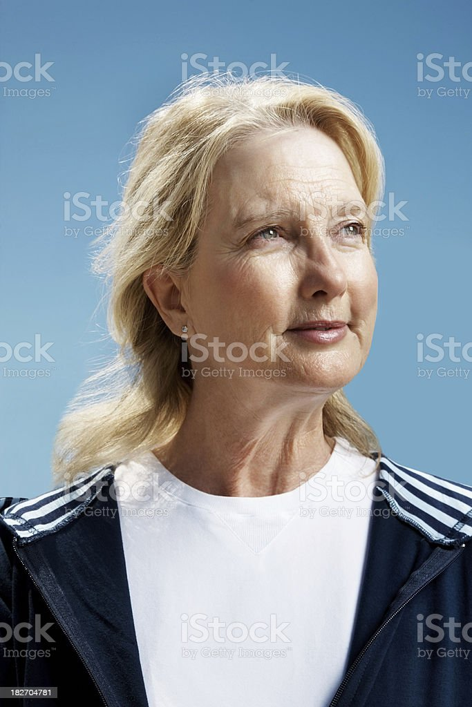 Retired blond female against the clear blue sky royalty-free stock photo