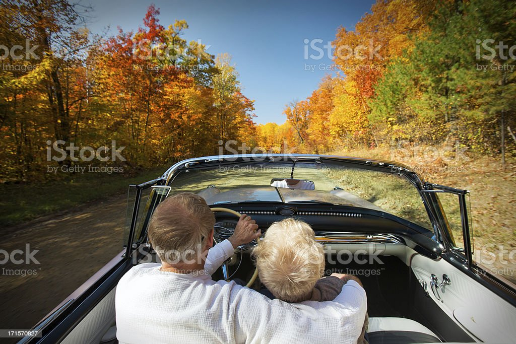 Retired couple enjoying an Autumn drive. stock photo