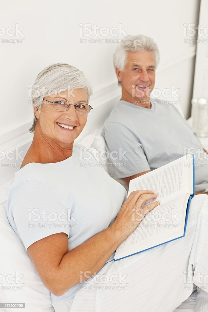 Retired couple in bed reading book royalty-free stock photo
