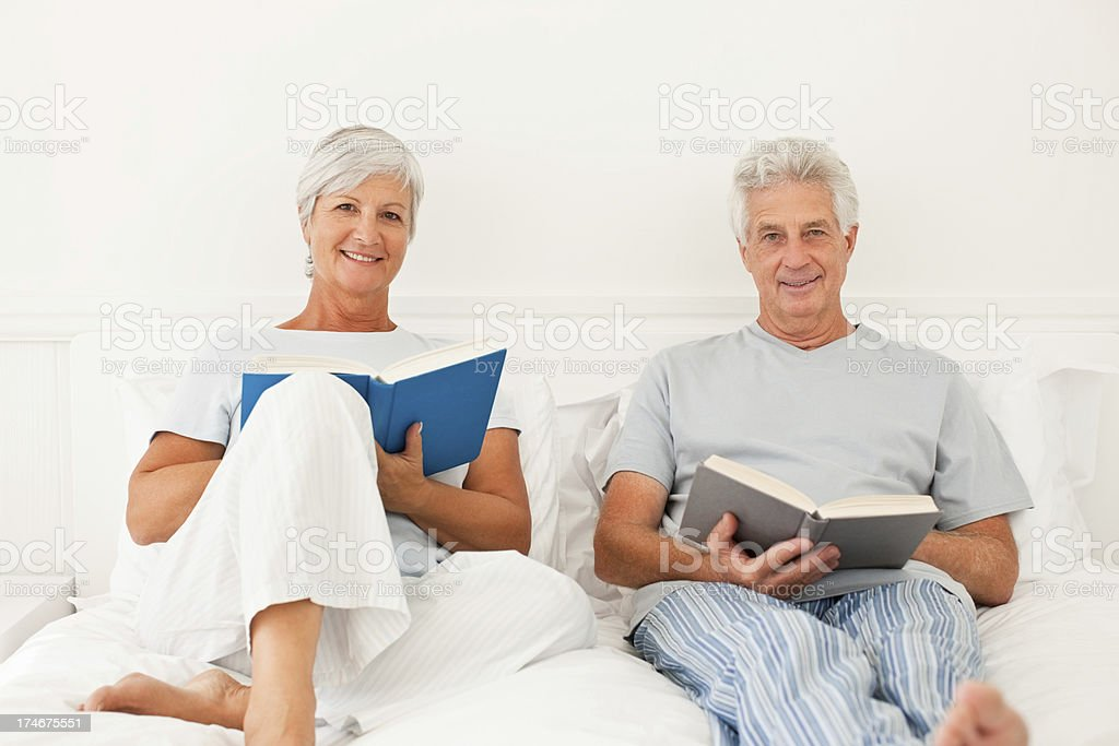 Retired couple in bed reading book stock photo
