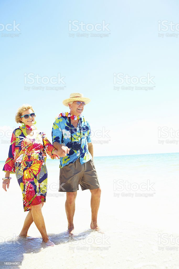 Retired couple laughing along the shore royalty-free stock photo