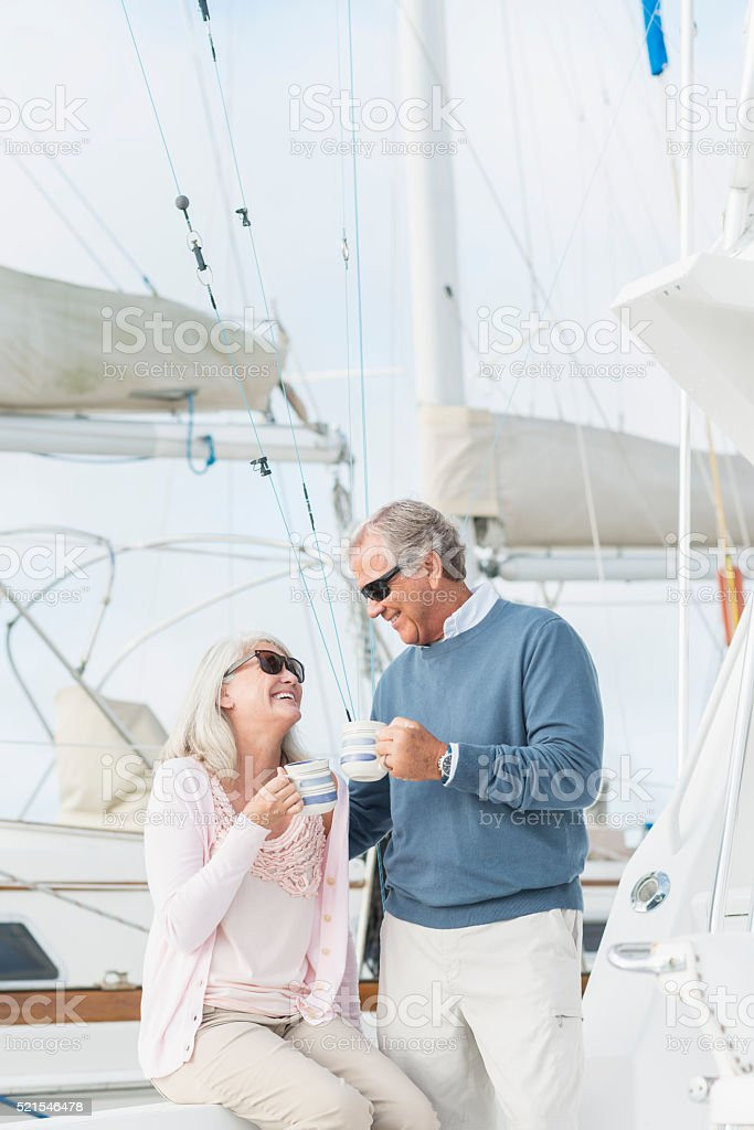 Retired couple on boat drinking coffee, talking stock photo