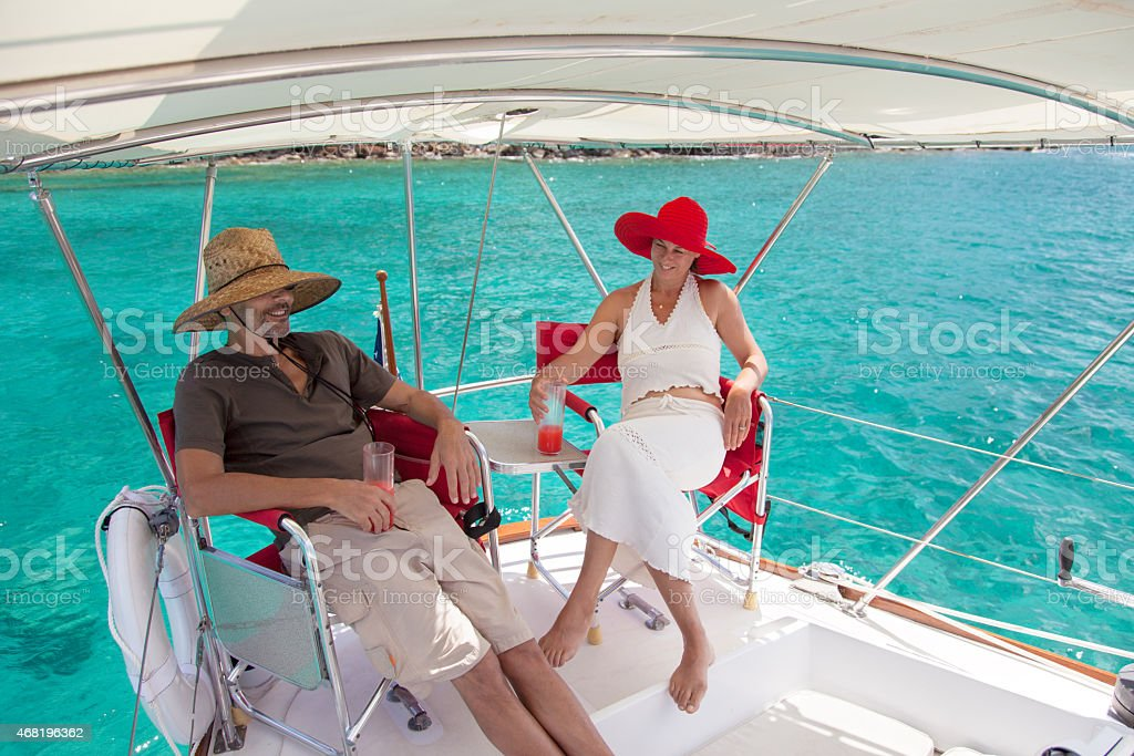 retired couple relaxing on a sailboat traveling through the Caribbean stock photo