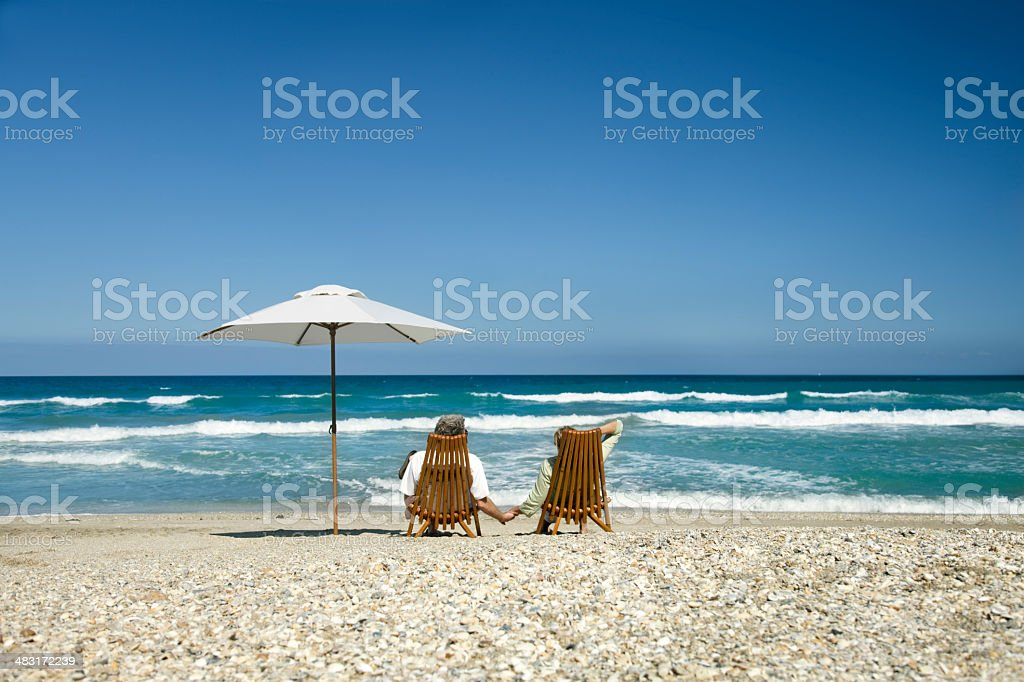 retired couple relaxing on beach stock photo