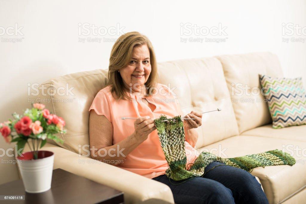 Retired elderly woman doing some knitting stock photo
