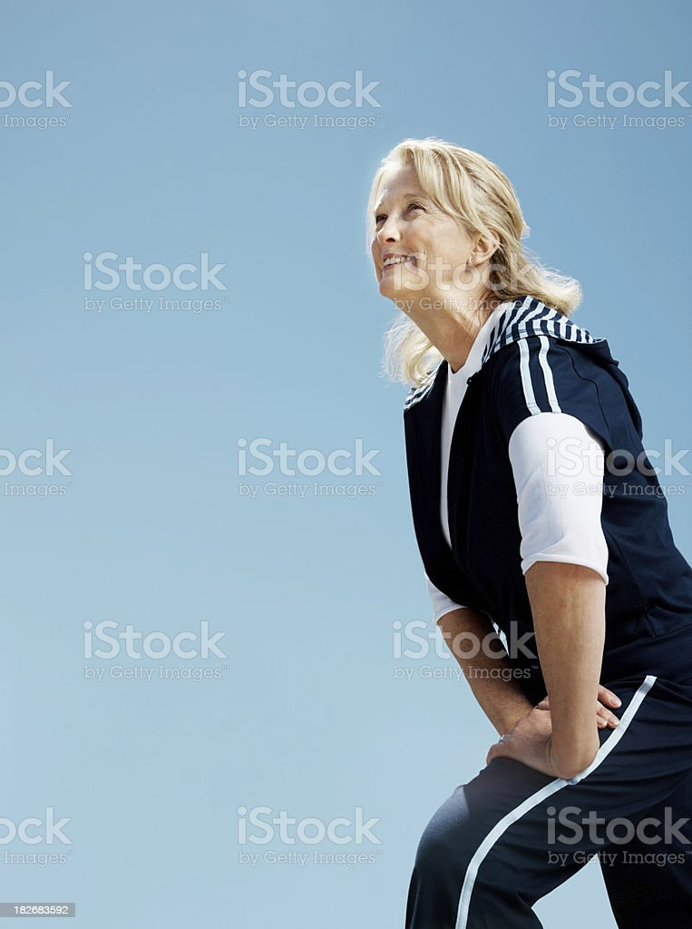 Retired female stretching against the clear sky royalty-free stock photo