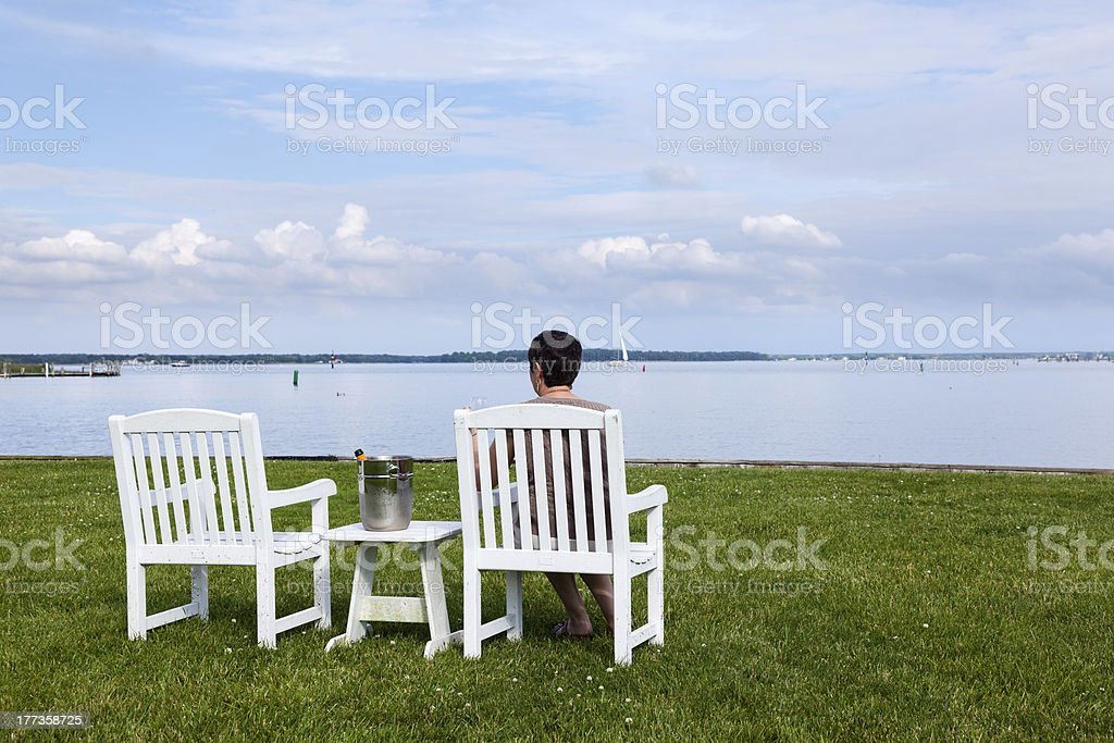 Retired lady by bay with champagne royalty-free stock photo