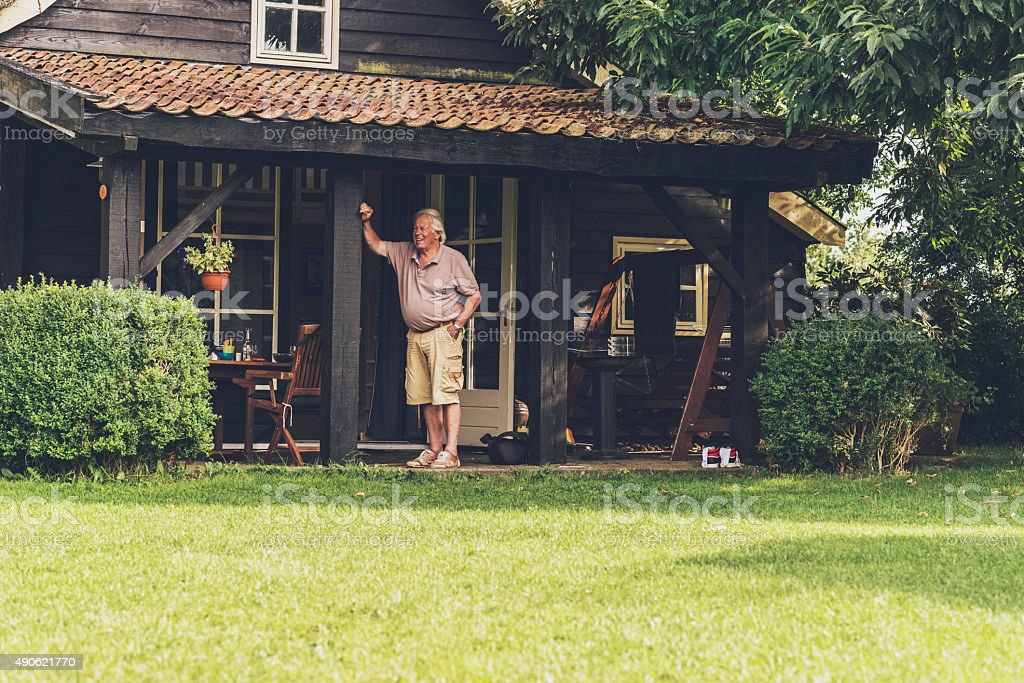 Retired man standing under porch of wooden house. stock photo