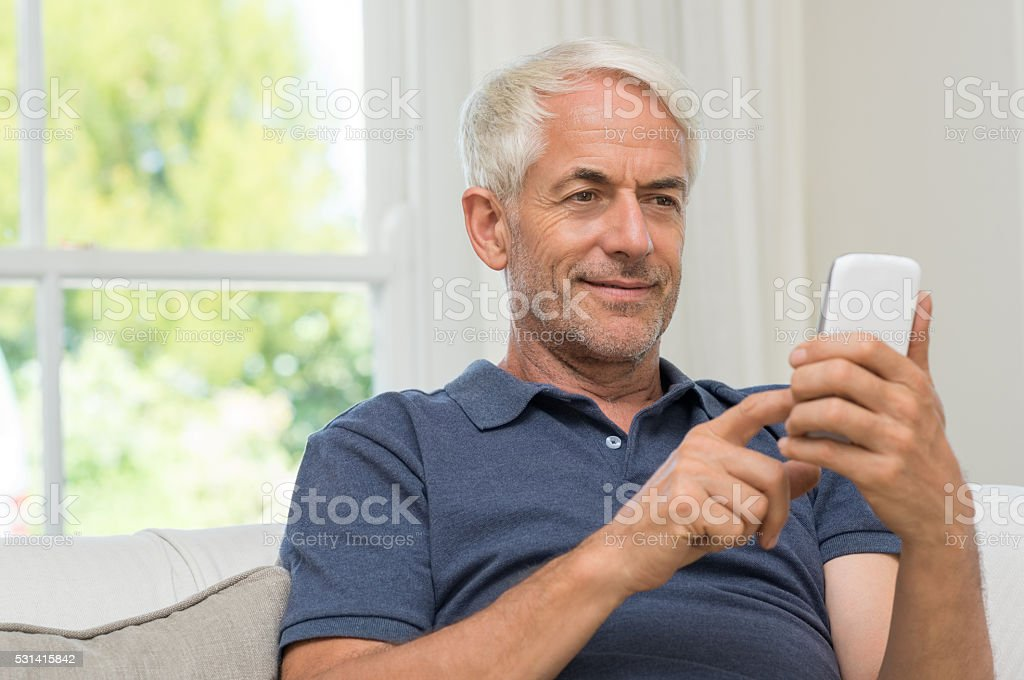 Retired man texting stock photo