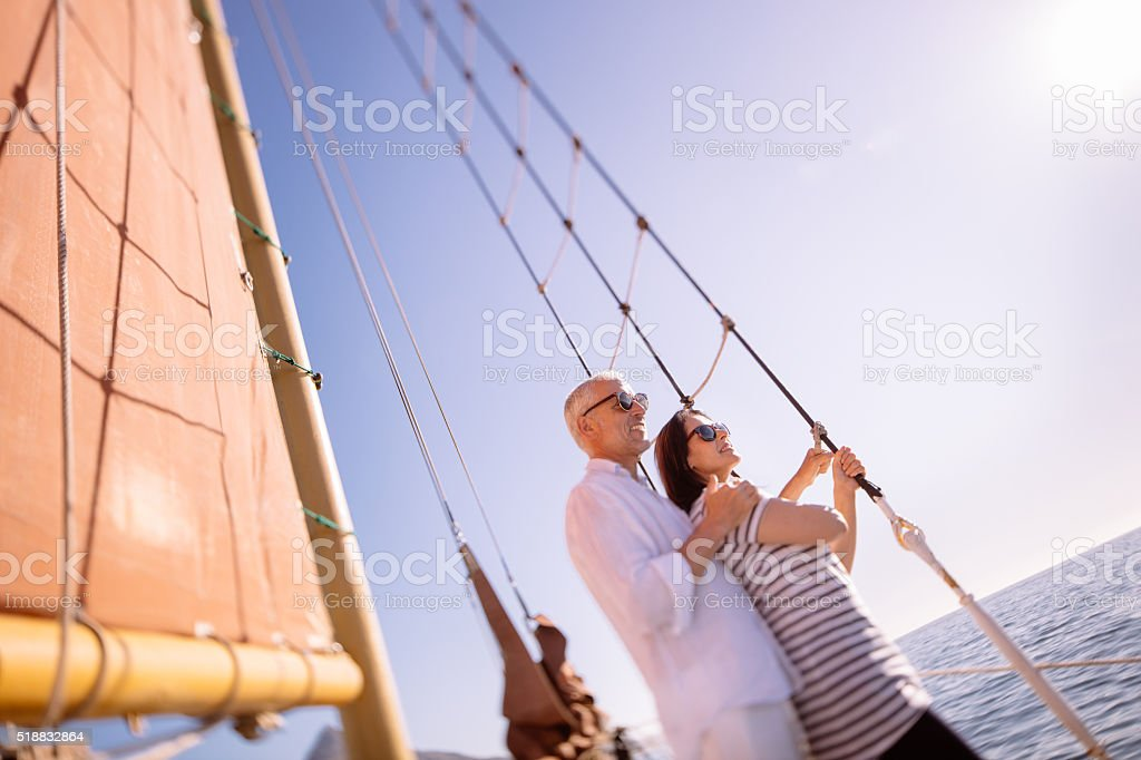 Retired mature couple on yacht with ocean and blue sky stock photo