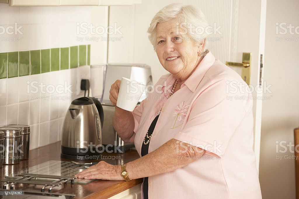 Retired Senior Woman In Kitchen Making Hot Drink royalty-free stock photo