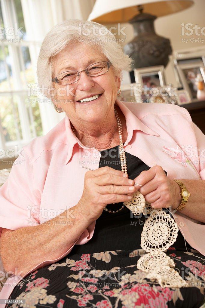 Retired Senior Woman Sitting On Sofa At Home Doing Crochet stock photo