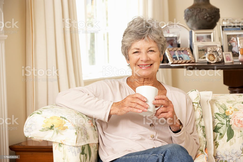 Retired Senior Woman Sitting On Sofa Drinking Tea At Home stock photo