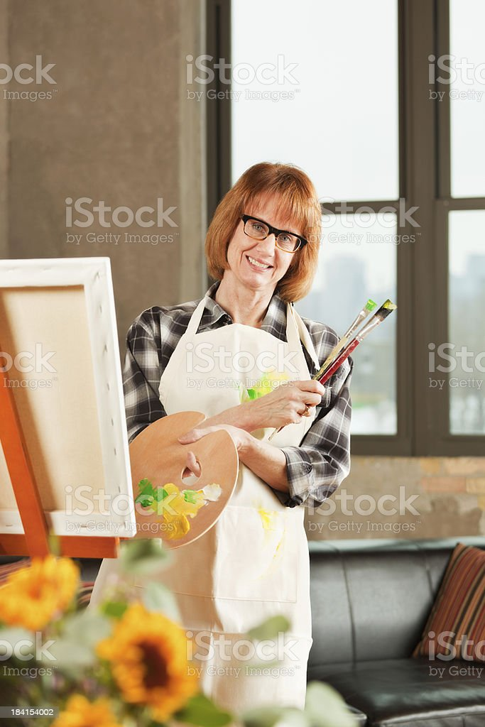 Retired Woman Hobby Painting on Canvas in Condominium Apartment Home royalty-free stock photo