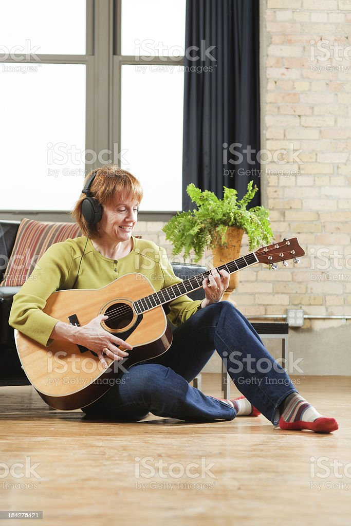 Retired Woman Playing Guitar Music Hobby in Condominium Apartment Home royalty-free stock photo