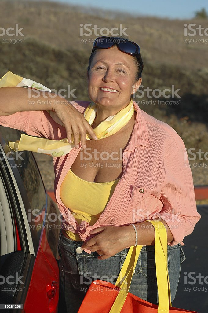 Retired woman with her red car royalty-free stock photo